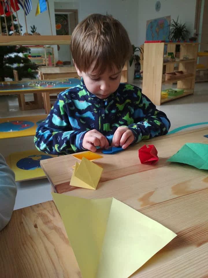 Мальчик делает оригами