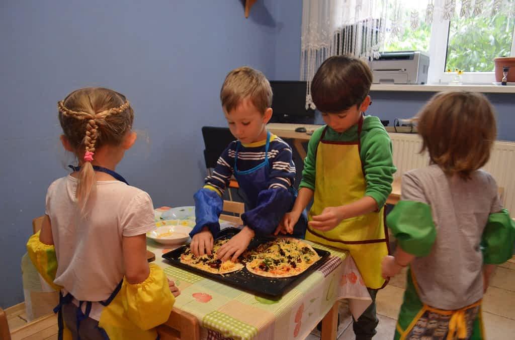 Дети украшают пиццу