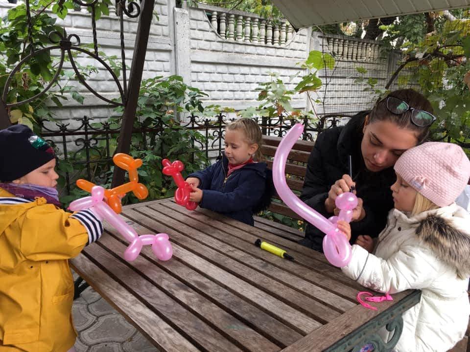 Педагог с детьми делает животных из шаров